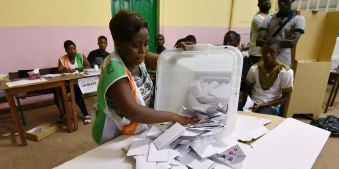 Une membre de la Commission électorale indépéndante (CEI) vide une urne, dans un bureau de vote du Plateau, à Abidjan, le 18 décembre 2016.