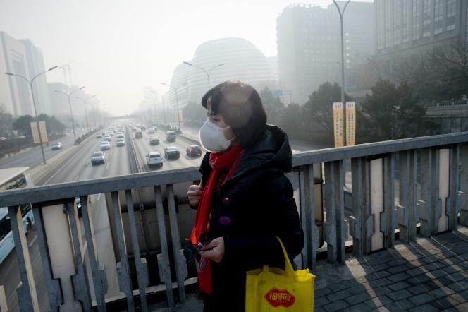 Une femme porte un masque pour se protéger de la pollution, à Pékin, le19décembre2016.