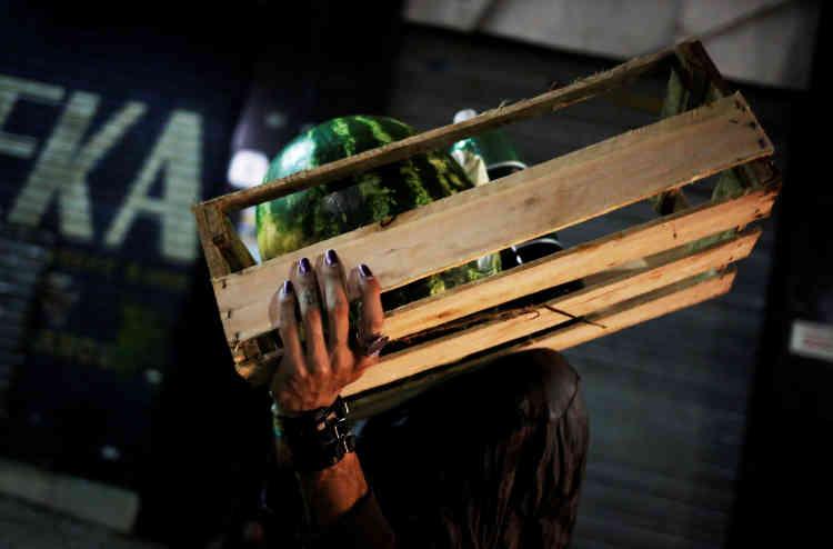 Rodrigo porte une caisse de fruits après la collecte des dons du marché municipal, dans le centre de Sao Paulo.