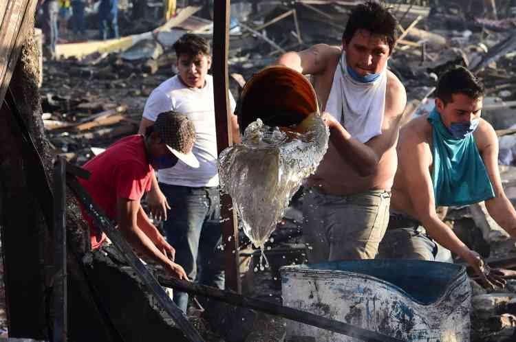 Des hommes tentent d'éteindre les cendres de l'incendie, sur le marché deTultepec, le20décembre.