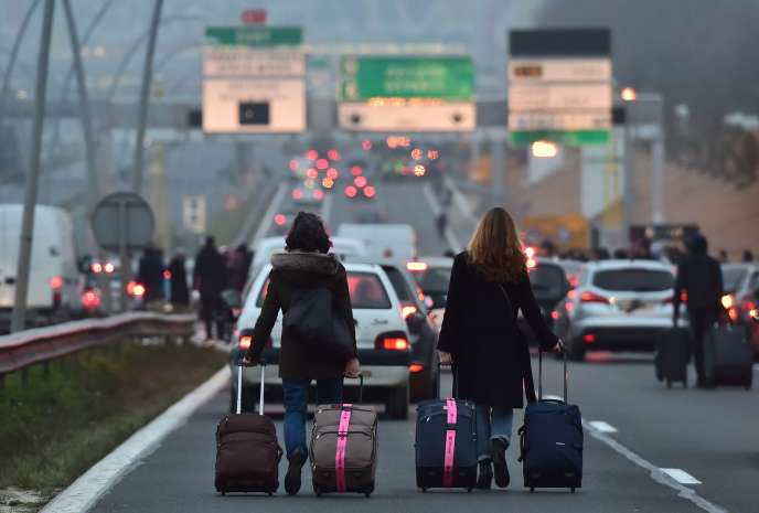 Des passagers avec leurs bagages rejoignent à pied l'aéroport d'Orly alors que des chauffeurs de VTC en bloquent l'accès, le 17 décembre.