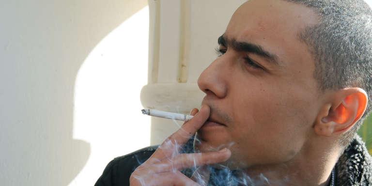 Weld El 15 fume une cigarette à l'entrée du tribunal de Hammamet,lors de son procès en appel, le 5 décembre 2013.