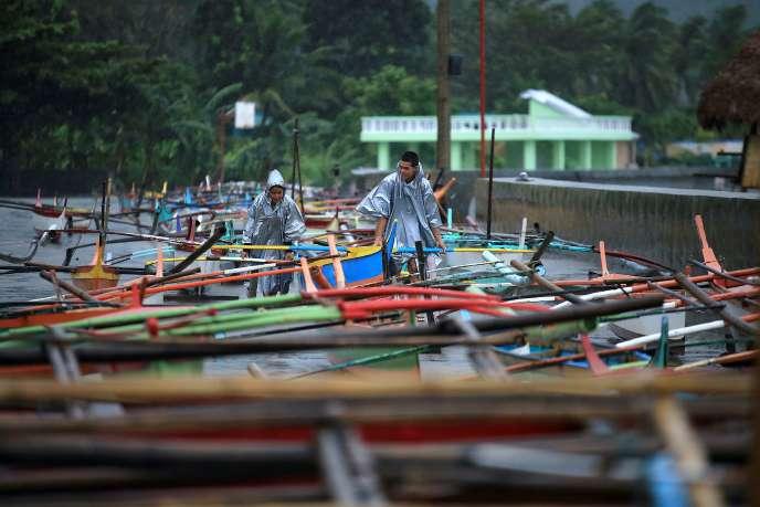 Les pêcheurs philippins attachent leurs bâteaux à l'arrivée du typhon Nock-Ten, le25décembre2016.