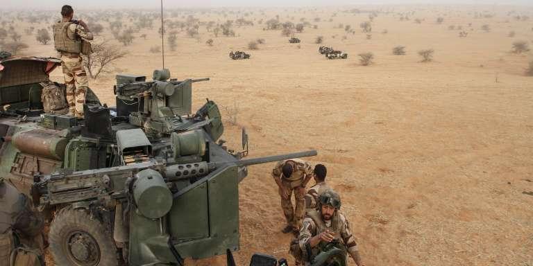 Des soldats français de l'opération Barkhane progressent dans le désert après une nuit de marche.