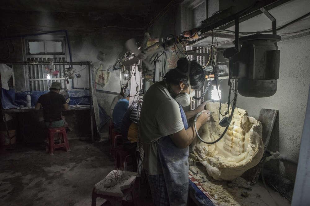 Des ouvriers au travail dans un atelier de sculpture de coquilles de bénitiers géants, dans le port de Tanmen, sur l'île de Hainan, au sud de la Chine, le 22 septembre.