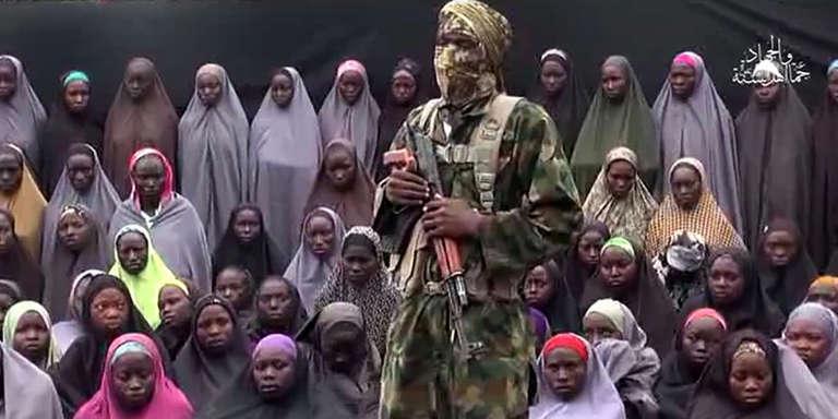 Sur cette image, extraite d'une vidéo attribuée à Boko Haram, un combattant du mouvement islamiste pose, en un lieu tenu secret, devant un groupe de jeunes filles enlevées à Chibok (nord-est du Nigeria), en avril 2014.