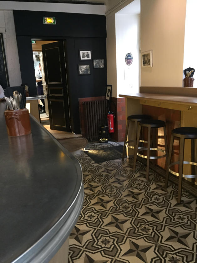 Une dizaine de tabourets se trouvent autour du bar et des tablettes.