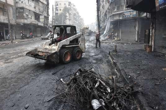 Un tracteur du régime syrien évacue les débris d'un quartier d'Alep tenu auparavant par l'opposition, le 27 décembre.