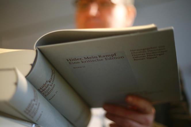 Le propriétaire d'une librairie feuillette un exemplaire de « Mein Kampf » réédité, à Munich, le 8 janvier 2016.
