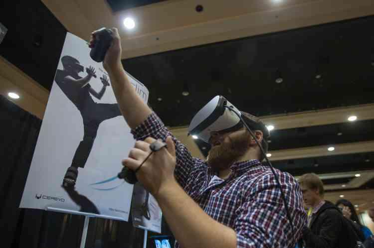 Un homme expérimente le système de réalité virtuelle Taclim. Ilporte des gants et des chaussures VR équipés dedispositifs tactiles qui fournissent une rétroaction haptique, c'est-à-dire donnant l'illusion du toucher.