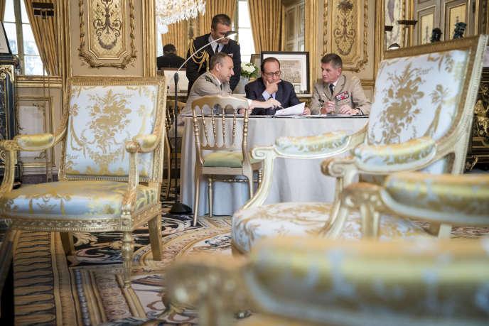 François Hollande en réunion avec le général Pierre de Villiers (à gauche), chef d'état-major des armées, et Benoît Puga, son chef d'état-major particulier, en octobre 2014.