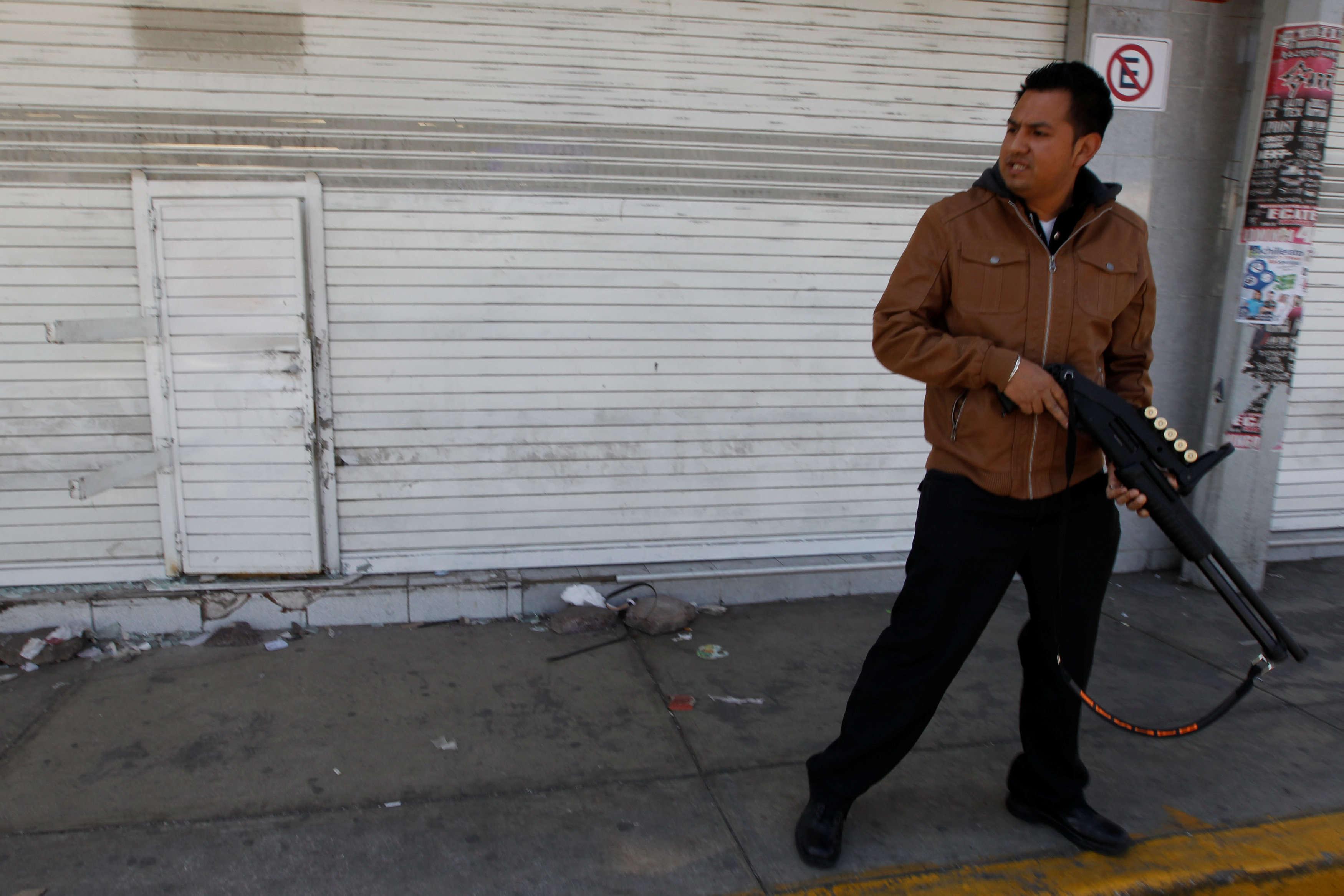 Un policier garde un magasin d'articles ménagers qui a été pillé à Ecatapec, le 5janvier. Le 6, en début d'après-midi, le prix du baril de « light sweet crude » (référence américaine du brut) augmentait de 41cents, le portant à 54,17dollars.