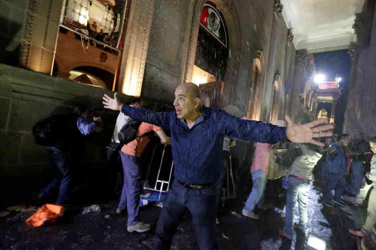 A Monterrey, un homme exhorte les manifestants à se calmer alors qu'ils vandalisent le Palacio de Gobierno (palais du gouvernement), au nord de la Macroplaza, le 5 janvier.