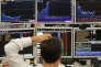Traders from ETX Capital work in central london on June 27, 2016. Shares in banks, airlines and property companies plunged on the London stock exchange Monday as investors singled out the three sectors as being the most vulnerable to Britain's decision to leave the EU. / AFP PHOTO / Daniel Leal-Olivas