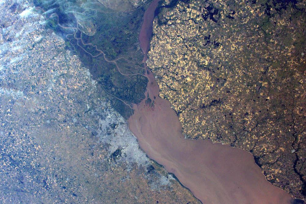 Buenos Aires est visible (la tâche grise) sur la rive australe de l'estuaire Rio de la Plata. Avec ses 12 millions d'habitants, la capitale de l'Argentine s'étend sur 100 km le long du Rio de la Plata. La couleur rougeâtre de l'embouchure est due aux sédiments brassés par les fleuves. Près de 60 millions de mètres cubes sont drainés chaque année. L'estuaire fait le lien et la frontière naturelle entre l'Argentine et l'Uruguay.
