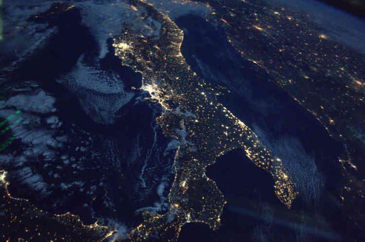 Reconnaissable au premier coup d'œil, la botte italienne scintille de l'espace. Près de huit mille kilomètres d'autoroutes ont été construits pour faciliter les liaisons nationales et internationales dans un territoire dit très accidenté (23% de plaines, 35% de montagnes et 42% en collines). Les deux gros points lumineux à l'ouest représentent les aires urbaines de Rome et de Naples. Avec ses 4 millions d'habitants, l'aire urbaine de Naples est l'une des plus grandes citées méditerranéennes, non loin derrière Rome qui compte plus de 4,3 millions d'habitants. Dépendante en énergie, l'Italie était la deuxième importatrice net d'électricité au monde (2014) et la troisième importatrice en gaz naturel au monde (2015).