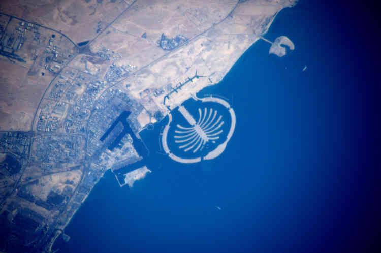 On reconnaît facilement ici le projet pharaonique de l'un des sept émirats : les îles artificielles de Dubaï, les Palm Islands, commencé en 2001. Nombreux architectes et ingénieurs ont salué les prouesses techniques et l'envergure du projet dirigé par le groupe immobilier Nakheel Properties. Le projet a nécessité l'extraction de 100 millions de tonnes de sable du fond du golfe Persique (et non du désert, trop fin pour la construction). Mais ces créations insulaires ont aussi suscité l'inquiétude des organisations écologiques comme WWF qui a alerté sur le danger des opérations de dragage et leur impact sur l'environnement marin. La crise financière qui a frappé Dubaï en 2009 a interrompu le projet.