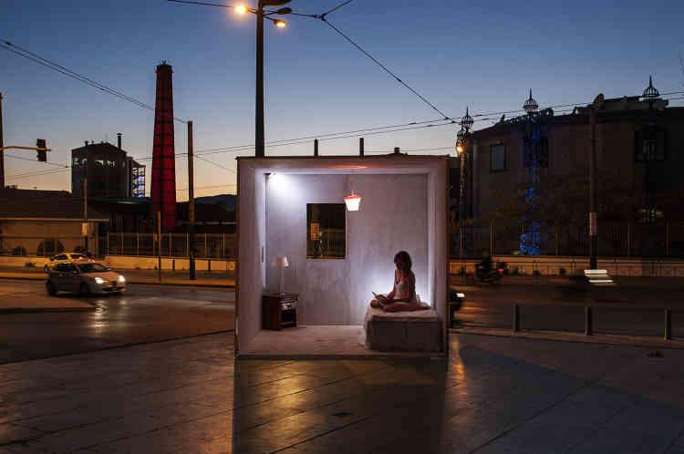 «Theodor Papadakis a placé un cube semblable à une pièce dans la ville. Il a proposé à des personnes de résider dans ce cube jusqu'à faire abstraction de l'environnement urbain et des passants. Il a capté des moments où la personne s'est sentie comme chez elle. Sa série d'images amène à nous interroger sur cette frontière entre sphère publique et sphère privée.»