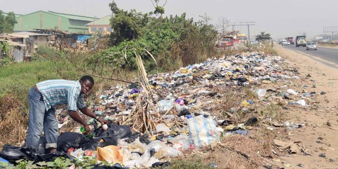 Un homme fouille les déchets dans une décharge le long de la voie express Lagos-Ibadan, le 4 janvier 2017.