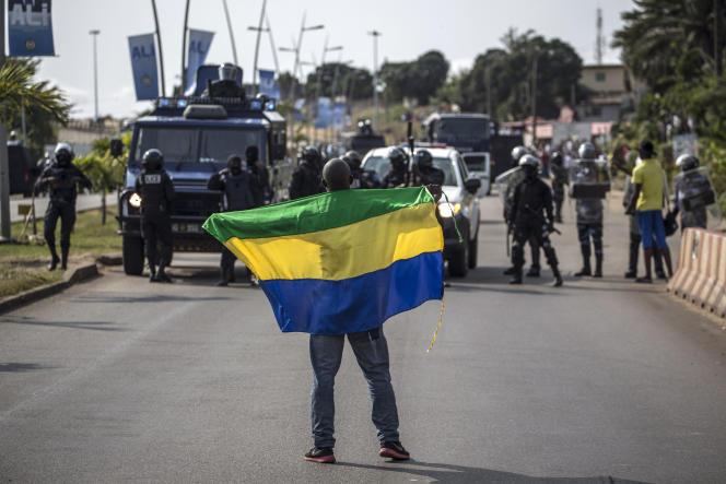 Le 31 août à Libreville, un supporteur de l'opposant Jean Ping, candidat à l'élection présidentielle contre Ali Bongo, fait face aux policiers antiémeute.