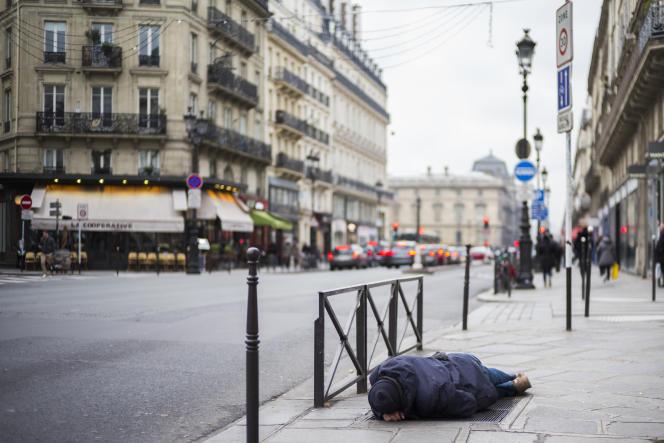 Un sans-abri dort sur une bouche d'aération du chauffage de la ville, à Paris, le 16janvier.