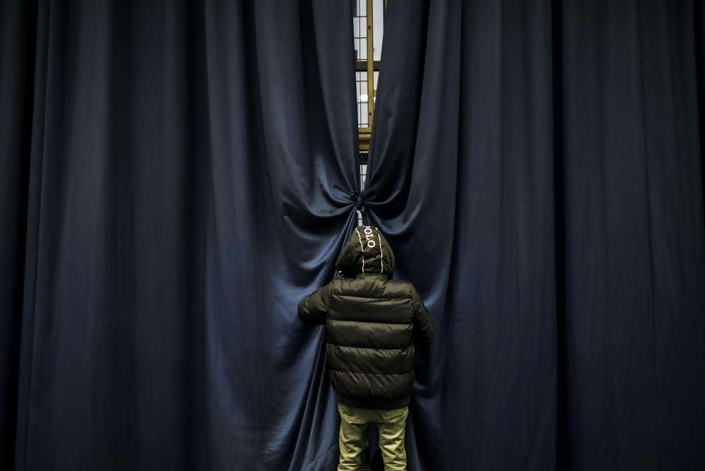 Un homme ferme des rideaux dans un gymnase où des familles sans-abris sont logées, le 5 janvier à Lyon. Les mesures du plan grand froid declenché par le gouvernement commencent à être appliquées dans la région.