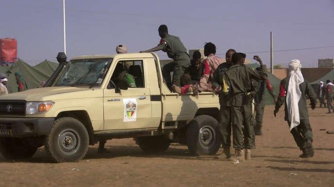 Des combattants maliens montent à bord d'une camionnette après l'attentat suicide qui a fait près de 60 morts dans un camp militaire de Gao, au nord du Mali le 18 janvier 2017.