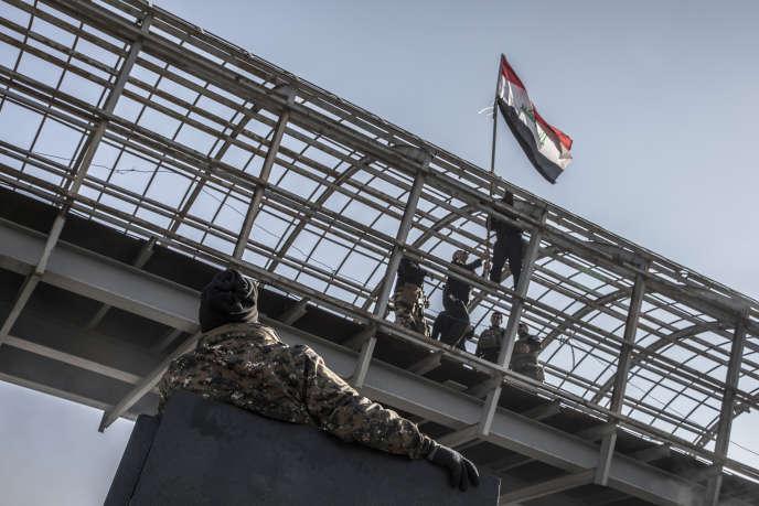 Les forces spéciales s'avancent dans le quartier Mohandessien, le dernier de sa mission dans la moitié Est de la ville de Mossoul. Elles acrochent le drapeau national sur un pont à proximité du Tigre. Mossoul, le 17 janvier.