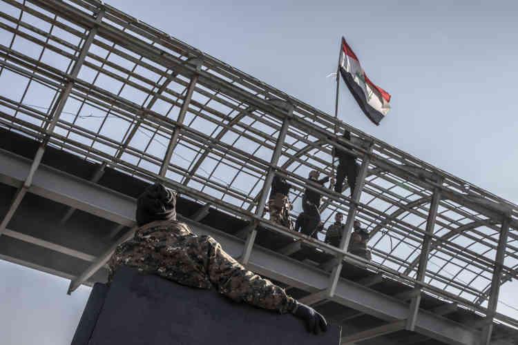 Les forces spéciales irakiennes accrochent le drapeau irakien sur un pont à proximité du Tigre dans le quartier Mohandessine.
