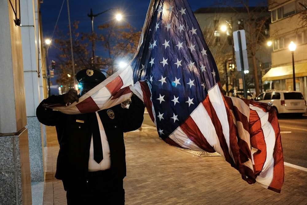 Un agent de sécurité lève le drapeau des Etats-Unis le matin de l'investiture, vendredi 20 janvier à Washington.