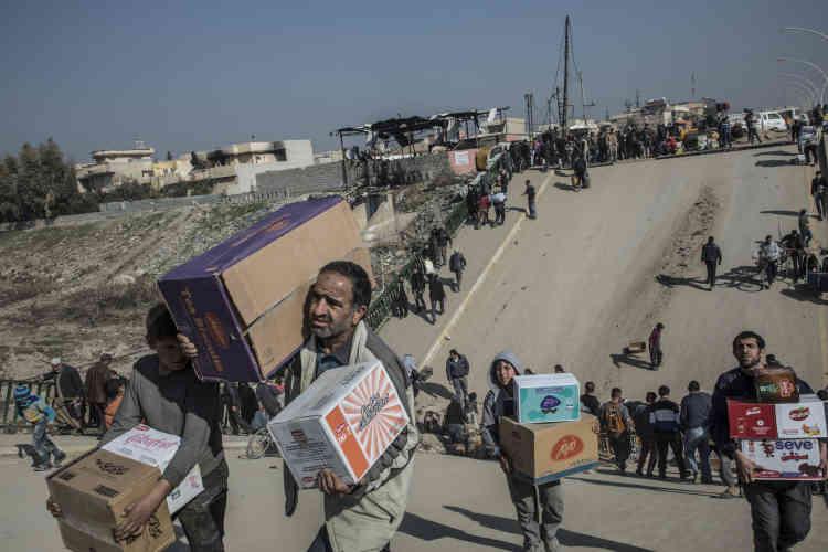 Les habitants empruntent un pont brisé par une frappe de la coalition pour passer des produits alimentaires.