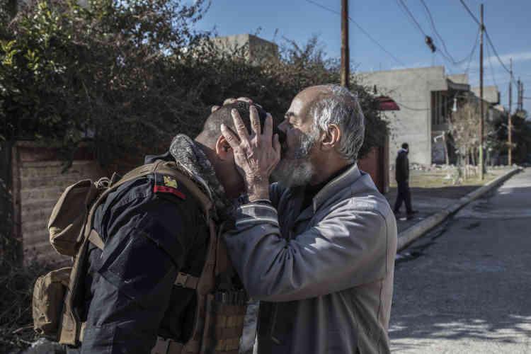 Un habitant de la partie est de Mossoul embrasse le front d'un membre des forces spéciales irakiennes à la libération du quartier Mohandeseen.