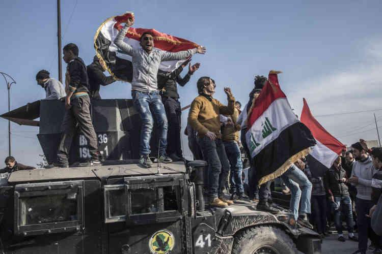 Une centaines de jeunes gens ont célébré les forces spéciales irakiennes, brandissant des drapeaux irakiens en chantant sur leurs véhicules blindés.