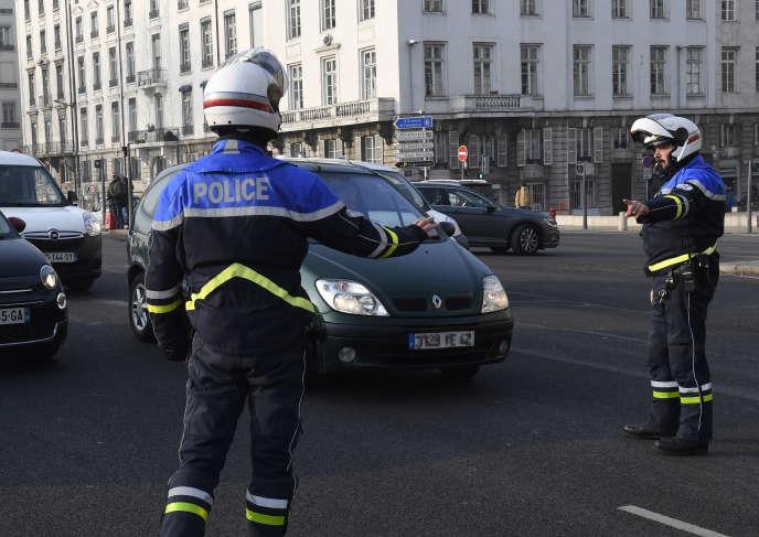 Des policiers contrôlent des véhiculesà Lyon, le 23janvier.