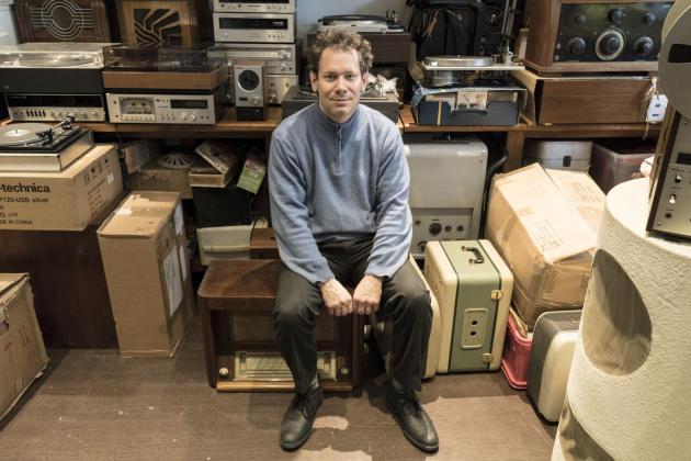 David Winter, collectionneur de vieilles consoles, dans sa boutique de réparation électronique à Paris, Paléophonies.
