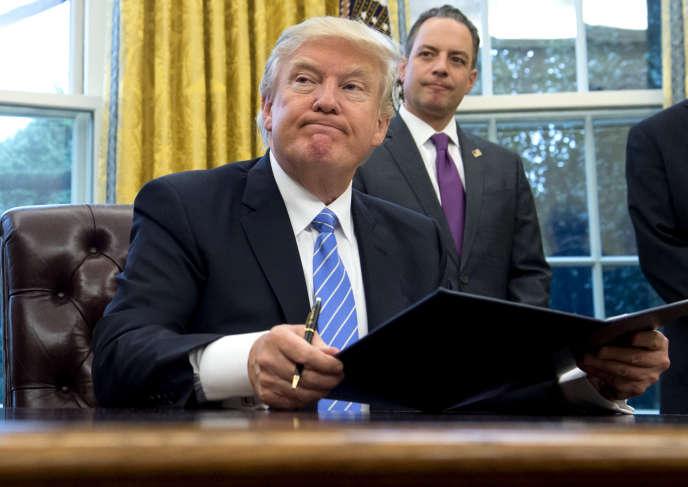 Le président des Etats-Unis, Donald Trump, lundi 23 janvier 2016, dans le bureau Ovale de la Maison Blanche où il signe une série de décrets.