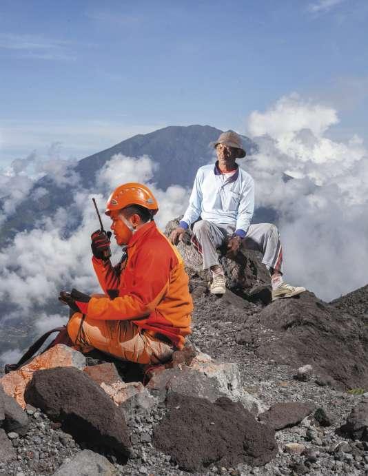 A 20 mètres du cratère du Merapi, à Java, un volcanologue (ici, avec son porteur) communique avec le technicien en train d'installer un GPS destiné à mesurer l'activité sismique du volcan.
