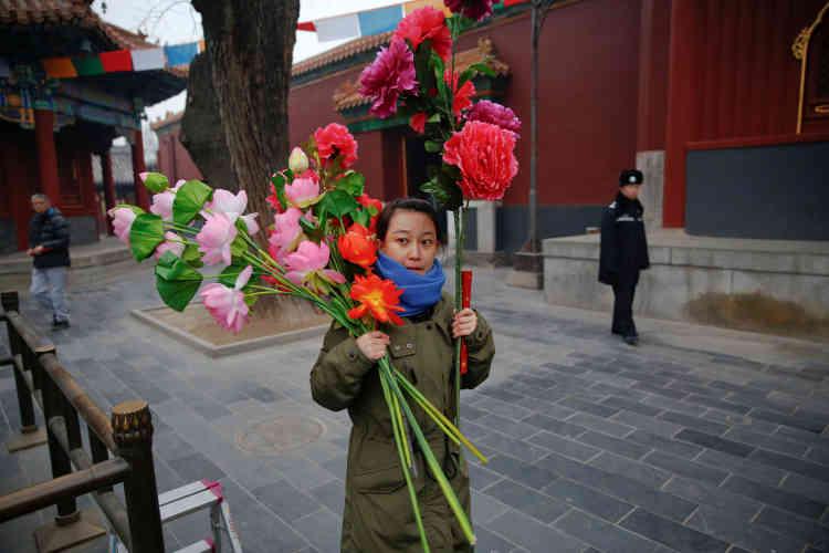 Une femme apporte des fleurs autemple de Yonghe, à Pékin, le 28 janvier, au premier jour du nouvel an lunaire chinois.