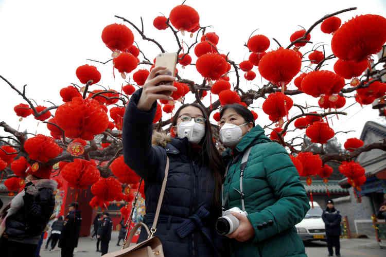 Des visiteuses du temple de la Terre, à Pékin, font des selfies, le 28 janvier.