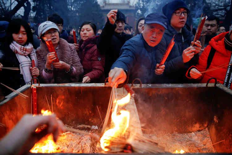 Des Pékinois allument des bâtonnets d'encens au temple de Yonghe, à Pékin, samedi 28 janvier.