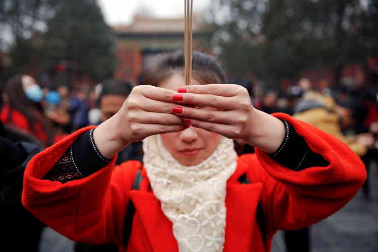 Une Chinoise prie, ses bâtonnets d'encens à la main, au temple de Yonghe, le28 janvier.