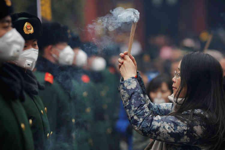 Une femme et ses bâtonnets d'encens, face à des policiers devant le temple de Yonghegong, samedi 28 janvier.