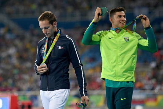 Thiago Braz exulte alors que Renaud Lavillenie descend du podium après avoir reçu la médaille d'argent au Jeux olympiques de Rio.