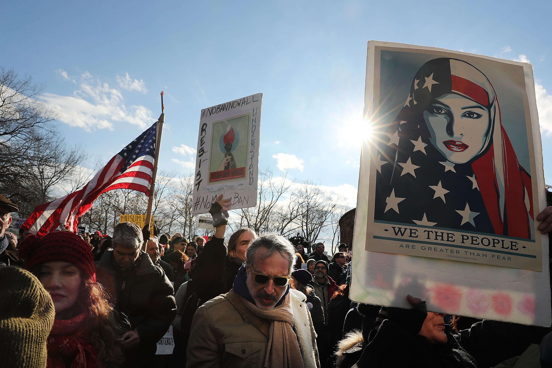 A New York, les manifestants se sont réunis à Battery Park,un parc donnant sur la statue de la Liberté. Ici, une femme brandit une pancarte où on peut lire « nous sommes plus grand que la peur» sous l'image d'une femme voilée avec le drapeau américain.