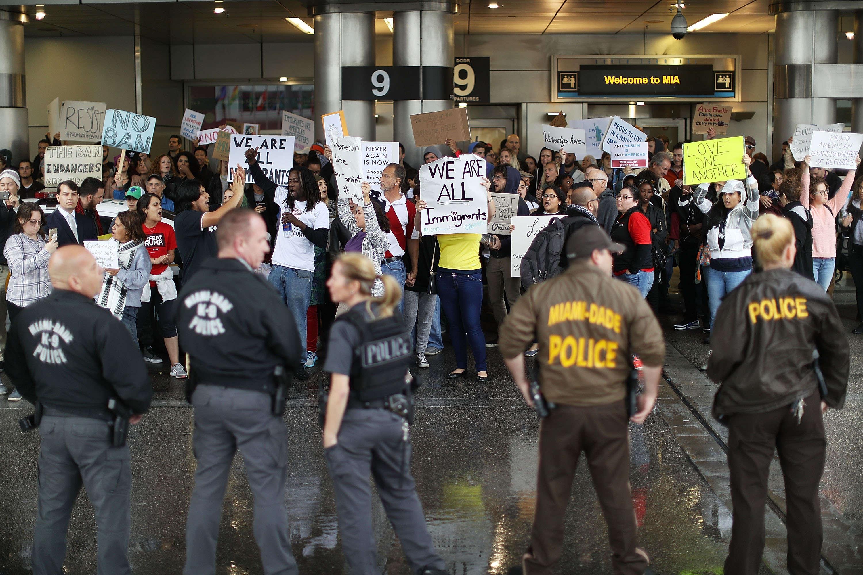 Des manifestants sont réunis à l'aéroport de Miami, où des policiers encadrent leur rassemblement, dimanche 29 janvier.