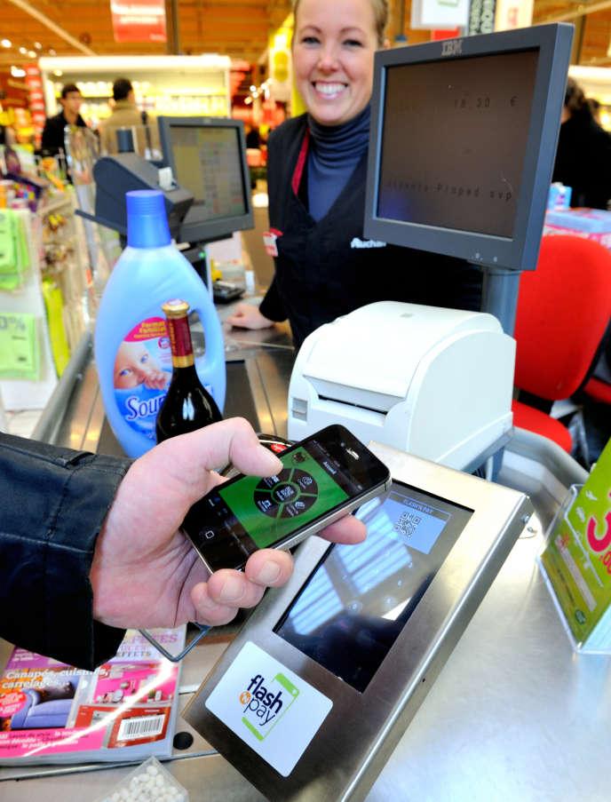 Un client paie à une caisse avec une application smartphone le 6 décembre 2012 dans un supermarché Auchan à Faches-Thumesnil près de Lille, dans le nord de la France.