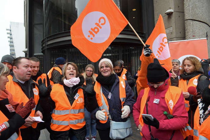 Employees of the Vivarte clothing group wave flags as they stage a demonstration outside the company headquarters in Paris on January 23, 2017. A crucial week starts on January 23 for the employees of the French fashion group Vivarte (La Halle, Andre, Caroll, San Marina), as they are called to protest against the drastic reorganisation of the group : nearly 2,000 jobs might be threatened. / AFP PHOTO / CHRISTOPHE ARCHAMBAULT