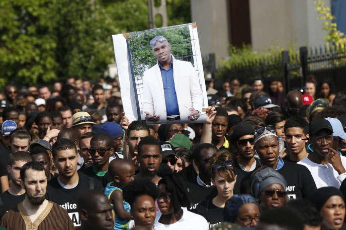 La foule rassemblée pour dénoncer la mort d'Adama Traoré après l'intervention des gendarmes brandit son portrait, le 22 juillet 2016, à Beaumont-sur-Oise.