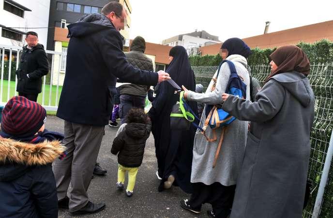 Le rectorat et la mairie distribuent des tracts d'information aux parents, devant l'école Al-Badr, à Toulouse, le 2 février.