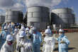 Members of the media, wearing protective suits and masks, walk after they receive briefing from Tokyo Electric Power Co. (TEPCO) employees (in blue) in front of storage tanks for radioactive water at TEPCO's tsunami-crippled Fukushima Daiichi nuclear power plant in Okuma town, Fukushima prefecture, Japan February 10, 2016. REUTERS/Toru Hanai - RTX26APO